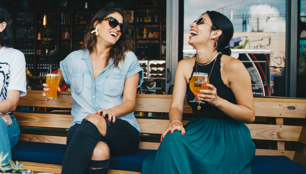 two women laughing while having a glass of beer