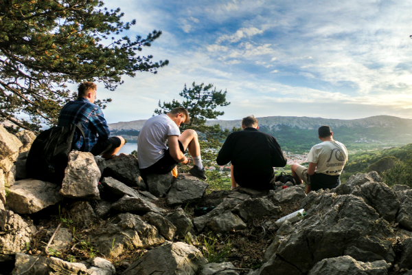 Men sitting down for a rest on a scenic mountainview stop during a hike
